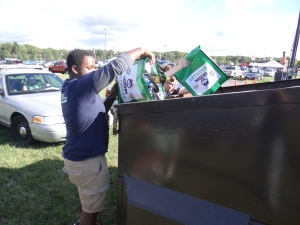 Volunteers empty their recycling bags into the single stream recycling dumpsters after collecting bottles and cans from tailgaters