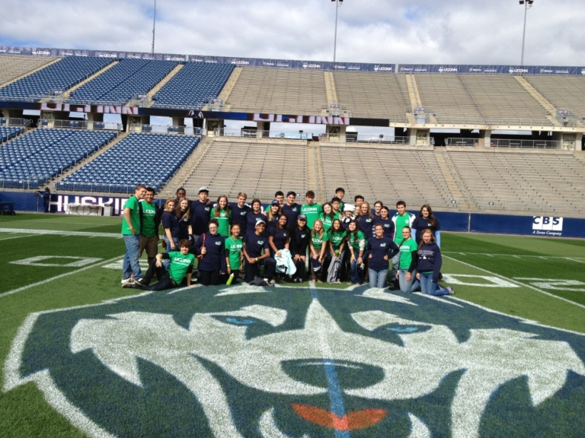 Green Game Day volunteers gather together on the field before  going out to collect recyclables from tailgaters